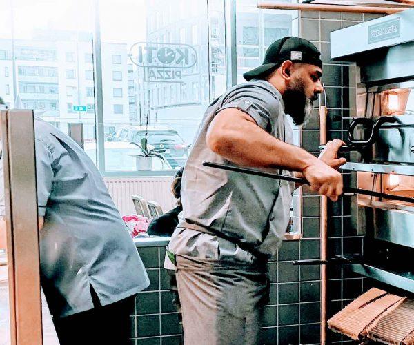 mies paistaa pizzaa